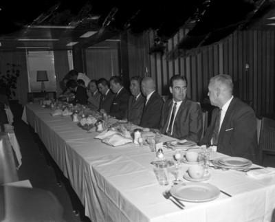 Hombres plátican en comedor durante una reunión