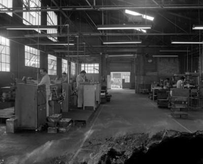 Obreros trabajan con refacciones automotrices en instalación industrial