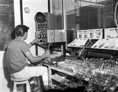 Trabajador opera un equipo eléctrico en una fábrica