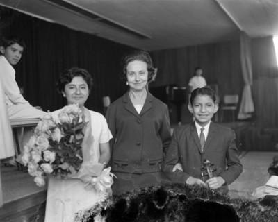 Eva Samano de López Mateos junto a niños en un auditorio después de festival escolar, retrato de grupo