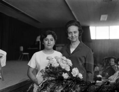 Eva Samano de López Mateos junto a un niño en un auditorio después de festival escolar, retrato