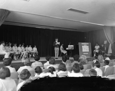 Niño pronuncia discurso durante festival escolar en un auditorio