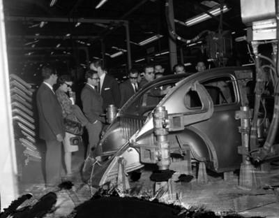 Ejecutivos observan carrocería de un automóvil en una fábrica