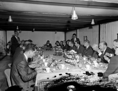 Hombres reunidos en un salón comen durante banquete