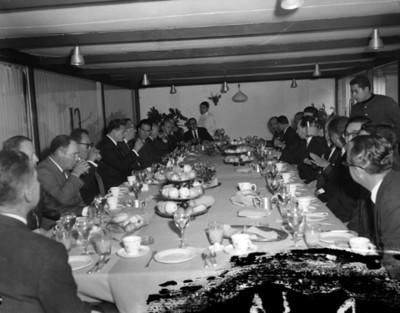 Empresarios conviven en comedor durante banquete en salón