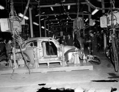 Hombres observan ensamblaje de automóvil en planta automotriz Volkswagen