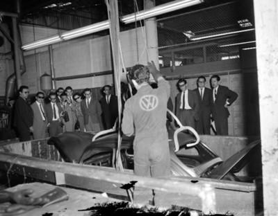 Visitantes observan carrocería de automóvil introducido en fasa en planta automotríz Volkwagen