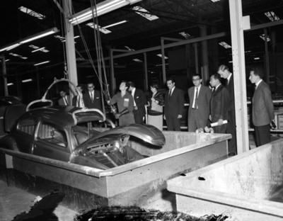 Visitantes observan carrocería de automóvil saliendo de fosa en planta automotríz Volkswagen
