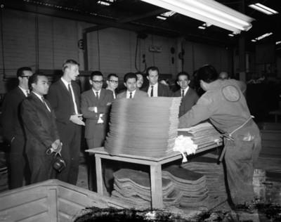 Hombres observan material de tapicería durante visita a planta automotríz Volkswagen