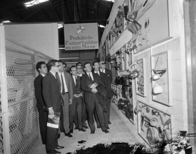 Hombres observan piezas de maquinaria expuestas en planta automotríz Volkswagen