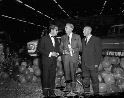 Empresarios conversan frente a automoviles Renault en exhibición