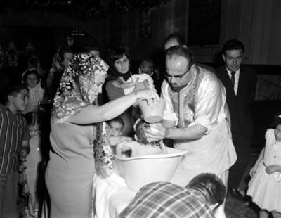 Sacerdote y mujer sostienen a niño en una tina, durante ceremonia de bautizo