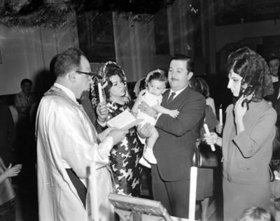 Sacerdote lee la biblia a un hombre cargando un niño durante bautizo