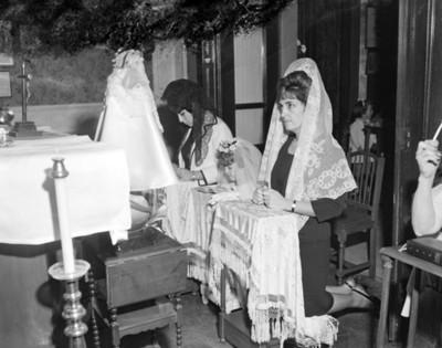 Mujeres y niña hincadas ante altar durante ceremonia religiosa