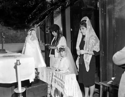 Mujeres acompañan a niña hincada ante altar durante ceremonia religiosa