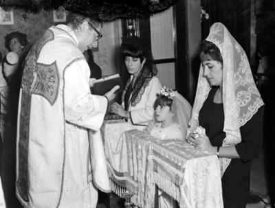 Sacerdote lee libro ante mujeres y niña hincadas durante ceremonia religiosa