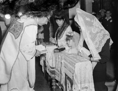 Sacerdote ante mujeres y niña hincadas durante ceremonia de primera comunión