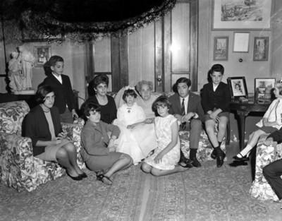 Familia reunida en sala durante festejo de primera comunión, retrato de grupo