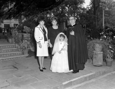 Mujeres y sacerdote acompañan a niña en día de su primera comunión, retrato de grupo
