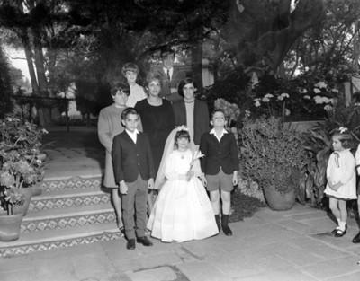 Familia acompaña a niña en día de su primera comunión, retrato de grupo