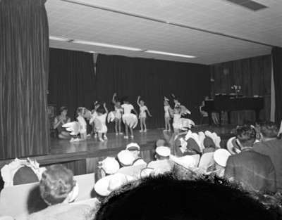 Niñas interpretan danza en escenario durante festival escolar