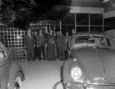 Sacerdote y hombres durante bendición de una agencia automotríz Volkswagen