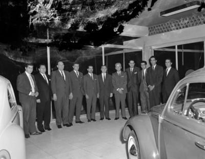 Ejecutivos de pie en la sala de exhibición de automóvilesen una agencia Volkswagen retrato de grupo