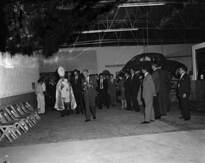 Sacerdote y gente durante bendición de un taller en una agencia automotríz Volkswagen