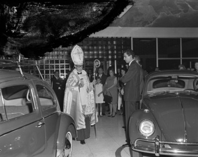 Sacerdote y gente durante bendición de una agencia automotríz Volkwagen