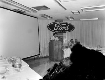 Hombre habla desde pódium durante conferencia de empresa ford