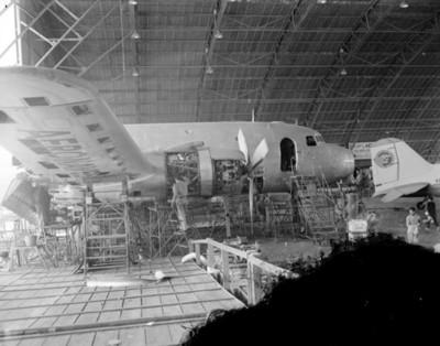 Obreros reparan maquinaria de avioneta en taller