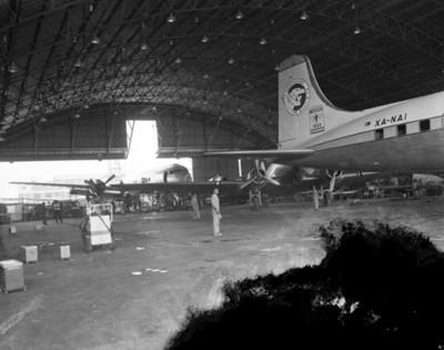 Obreros observan avionetas en taller de reparación