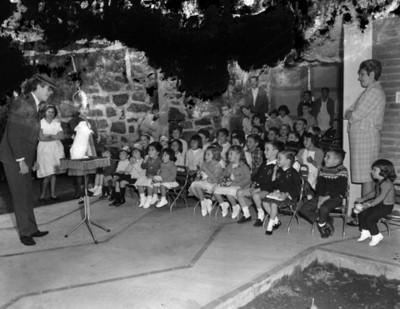 Niños observan a mago realizar acto de magia durante cumpleaños en el patio de una casa