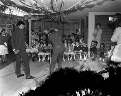 Niños y adultos observan acto de magia durante cumpleaños en el patio de una casa