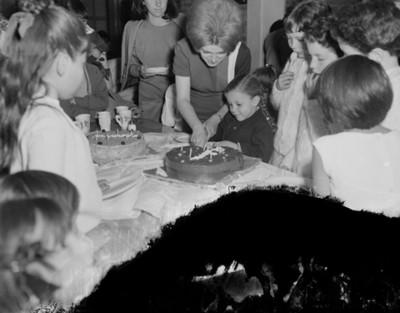 Niña corta pastel duranmte cumpleaños en el comedor de una casa