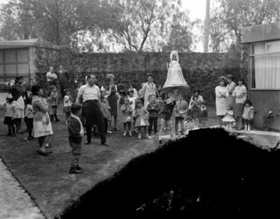 Niños rompen piñata durante cumpleaños en el patio de una casa