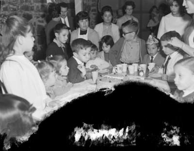 Niño sopla velas de un pastel durante cumpleaños en el comedor de una casa
