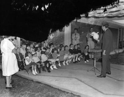 Niños observan a mago con un conejo durante cumpleaños en el patio de una casa