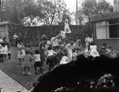 Hombre vacea dulces de una piñata a niños durante cumpleaños, en el patio de una casa