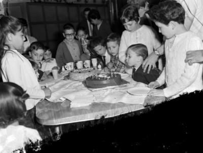 NIña sopla velas de un pastel durante cumpleaños en el patio de una casa