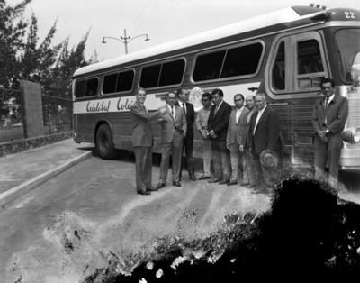 Ejecutivos de pie junto a un autobús en una calle, retrato de grupo