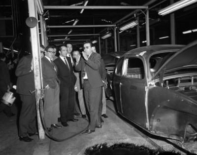 Empresarios conversan junto a carrocería de automovil durante visita a planta Voplkswagen
