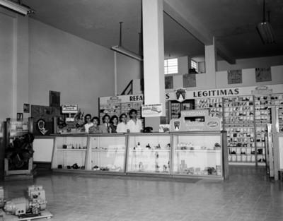 Empleados tras mostrador en tienda de refacciones automotrices, retrato de grupo