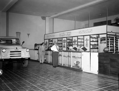 Hombres de pie junto al mostrador de una refaccionaria automotríz