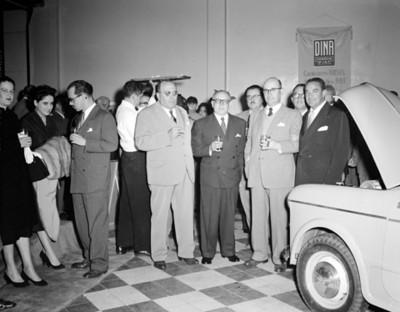 Empresarios junto a automovil en exhibición, retrato de grupo