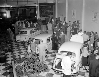 Gente entre automoviles en sala de exhibición
