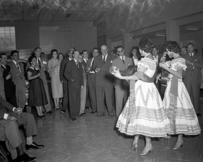 Gente observan a mujeres con trajes folclóricos y guitarras durante banquete en una agencia automotríz