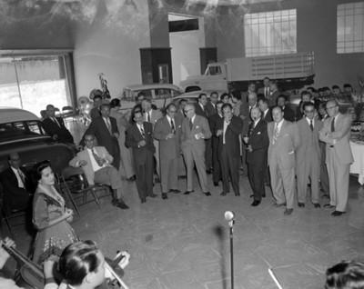 Hombres observan a una cantante y músicos durante banquete en una agencia automotríz