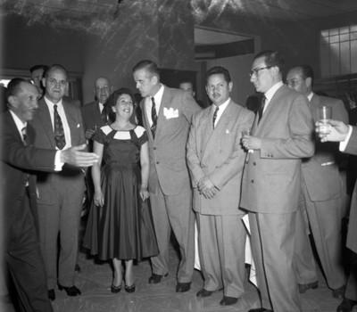 Hombres y mujer platican durante banquete en una agencia automotríz