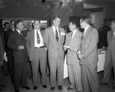 Hombres platican junto a mesa con comida durante banquete en una agencia automotríz